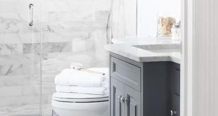 Beautiful bathroom features a dark gray vanity topped with carrera marble atop a...