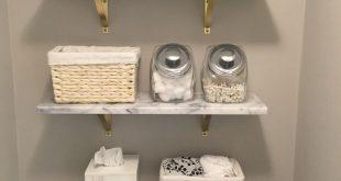 Wandregale aus Marmor von CB2. Holzregale und Toilettenpapier in einem Korb. Bau...